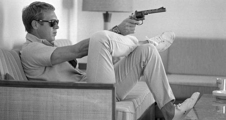 At his bungalow in Palm Springs, Steve McQueen practices his aim before heading out for a shooting session in the desert, 1963.